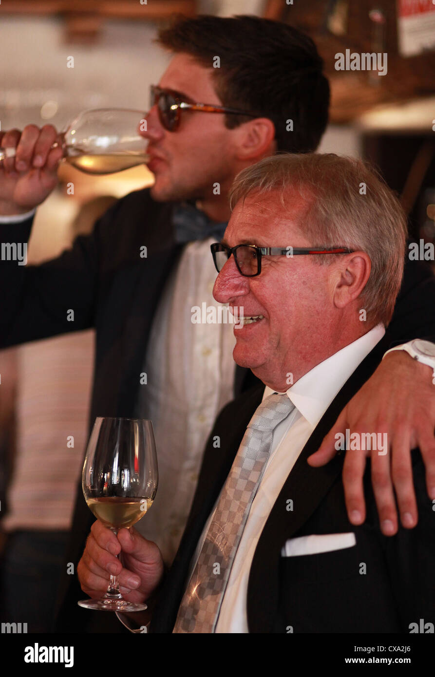 During a celebration in a wine bar two family members are drinking white wine. Spilimbergo, northern Italy, Europe. - Stock Image
