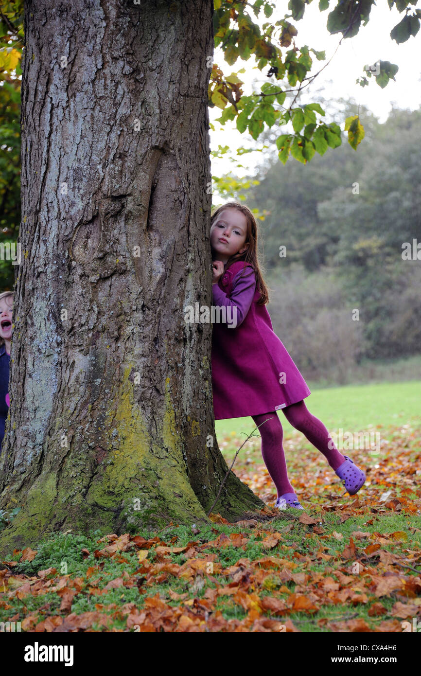Young girls peeks out from behind a tree during a game of hide and seek on Hubbard's Hills. - Stock Image