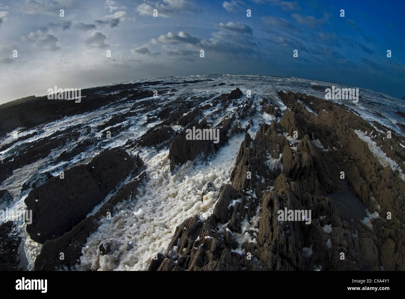 Spume covered rocks during a winter gale. Croyde Beach, North Devon, England. - Stock Image