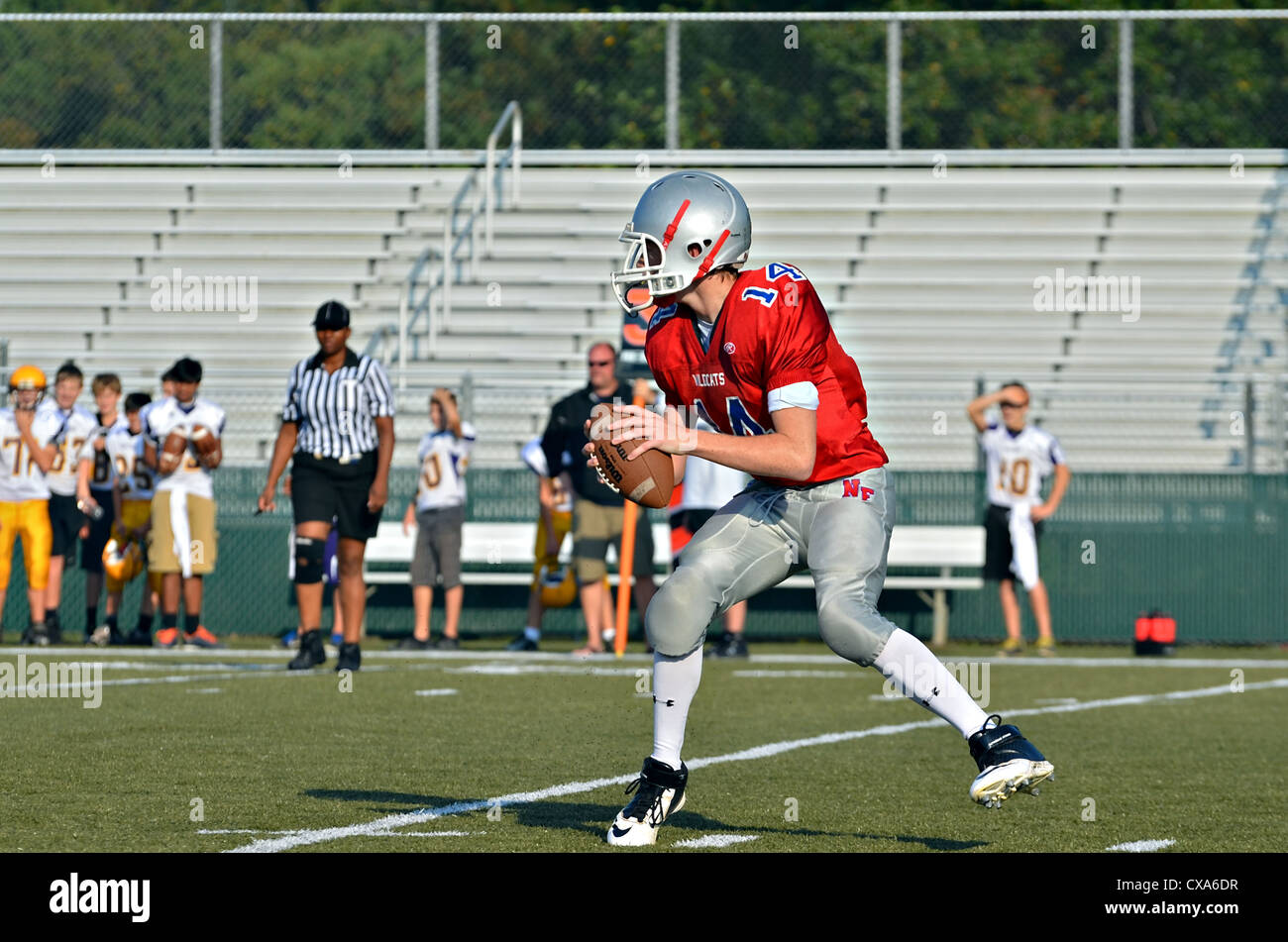 A  young quarterback ready to throw the ball during a football game, a referee closely following the action. - Stock Image