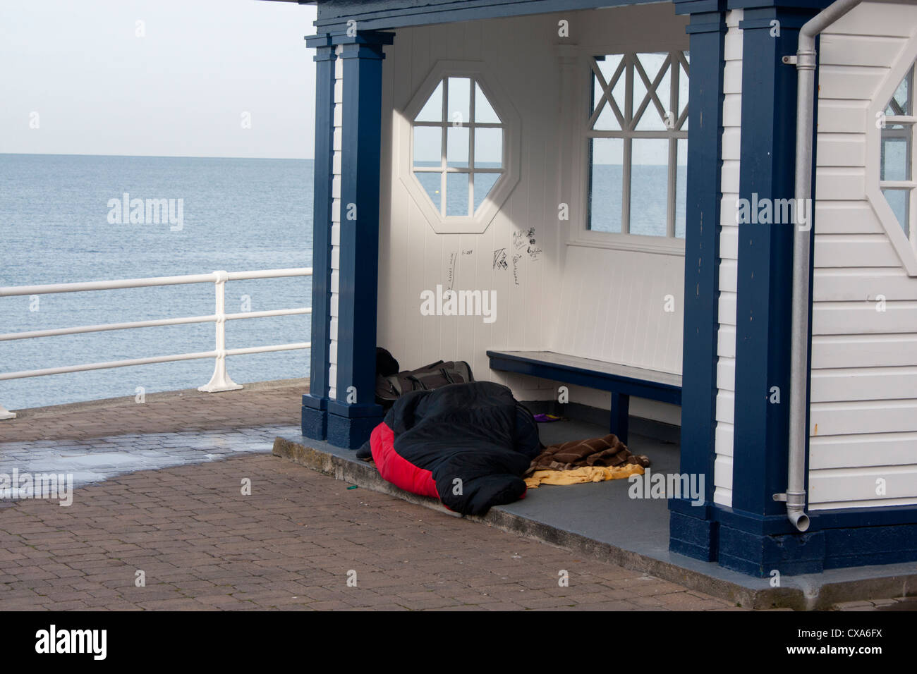 Homeless woman (hidden lying under sleeping bag) sleeping in shelter on promenade next to beach and sea Aberystwyth - Stock Image