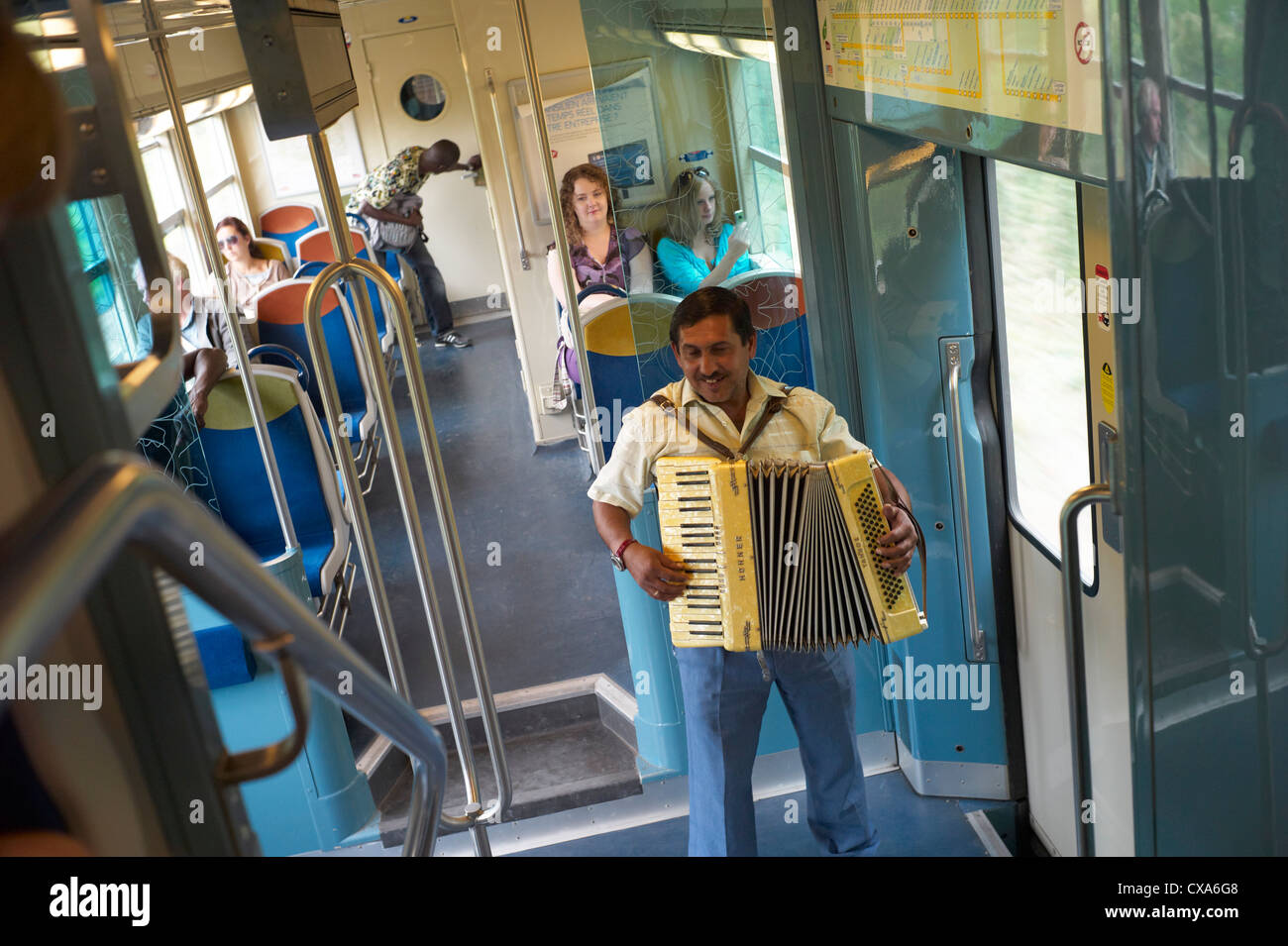 A gypsy or Roma man busking on a train between Paris and versailles with an accordian - Stock Image