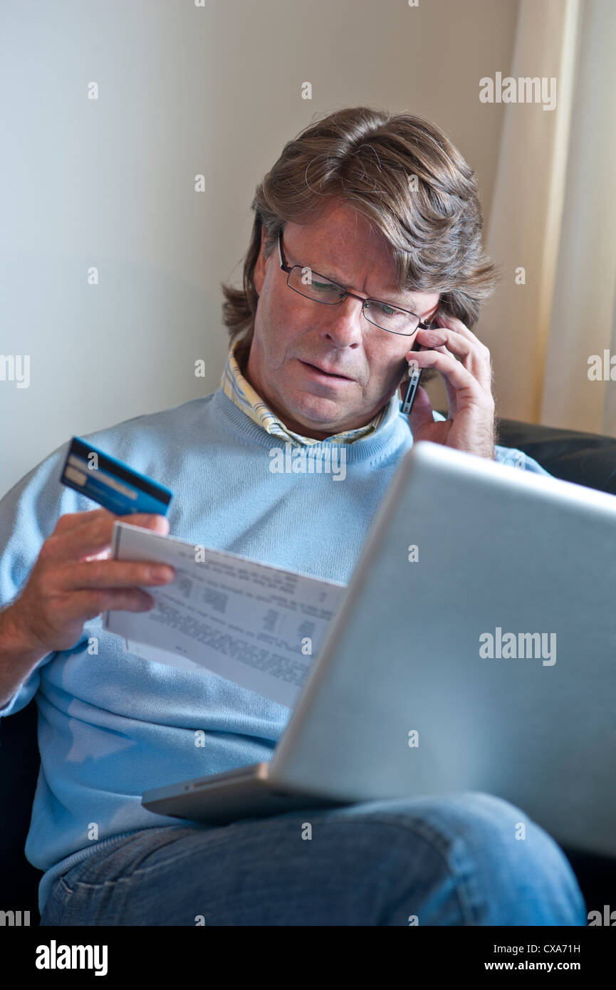 Worried mature man at home checking financial transactions using his laptop computer and an iPhone smartphone - Stock Image