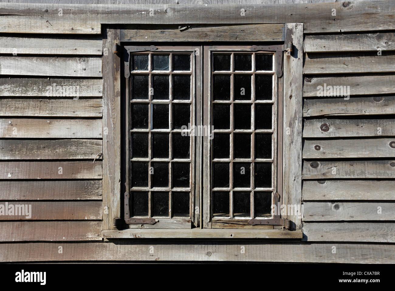 weathered clapboard siding window frame, Shelburne, Nova Scotia - Stock Image