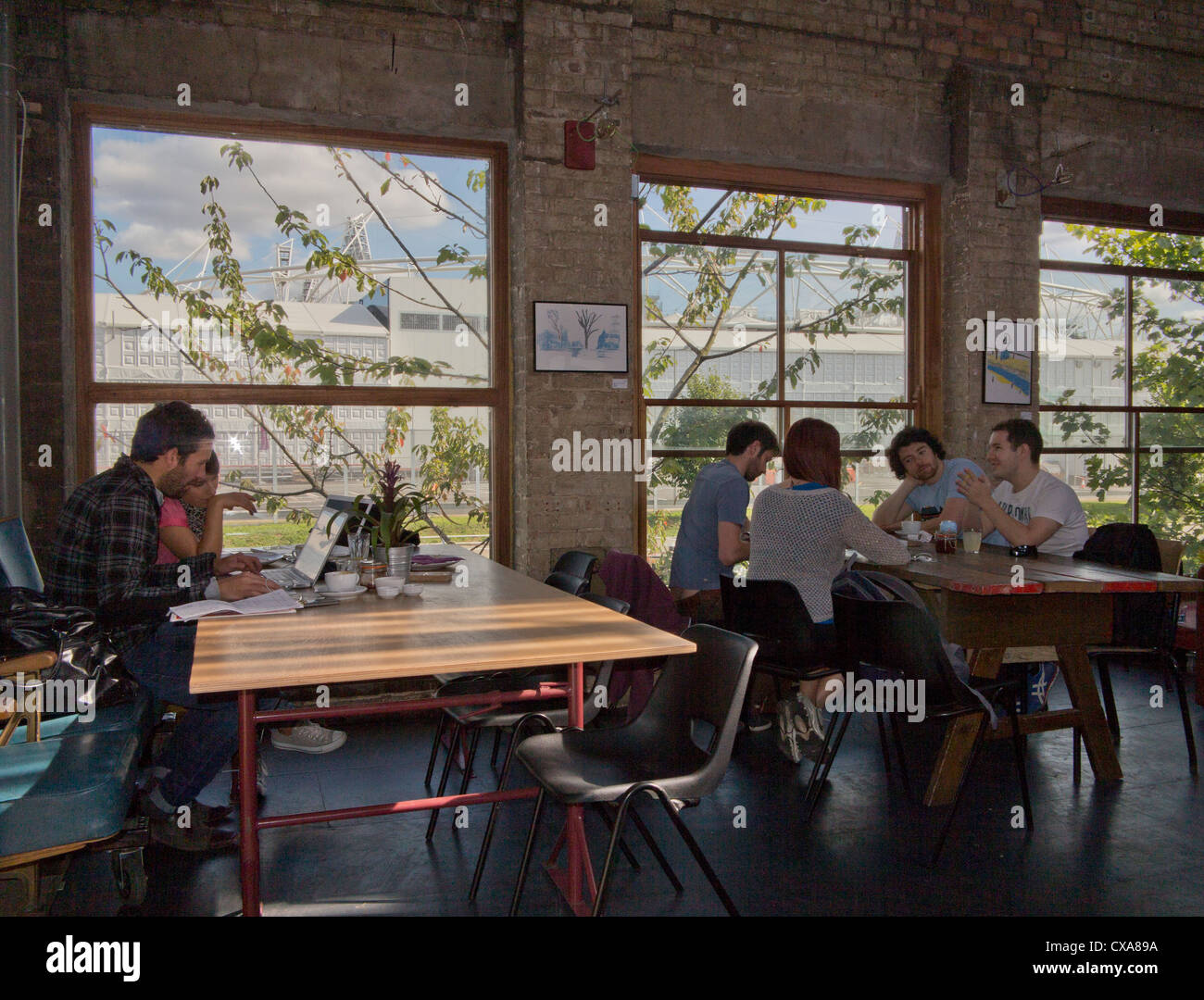 People enjoy drinks at cafe by new towpath on Regent's canal built as part of the legacy of the London 2012 - Stock Image