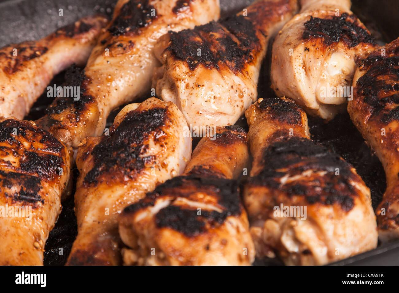 some juicy roast chicken drumstick on frying pan - Stock Image
