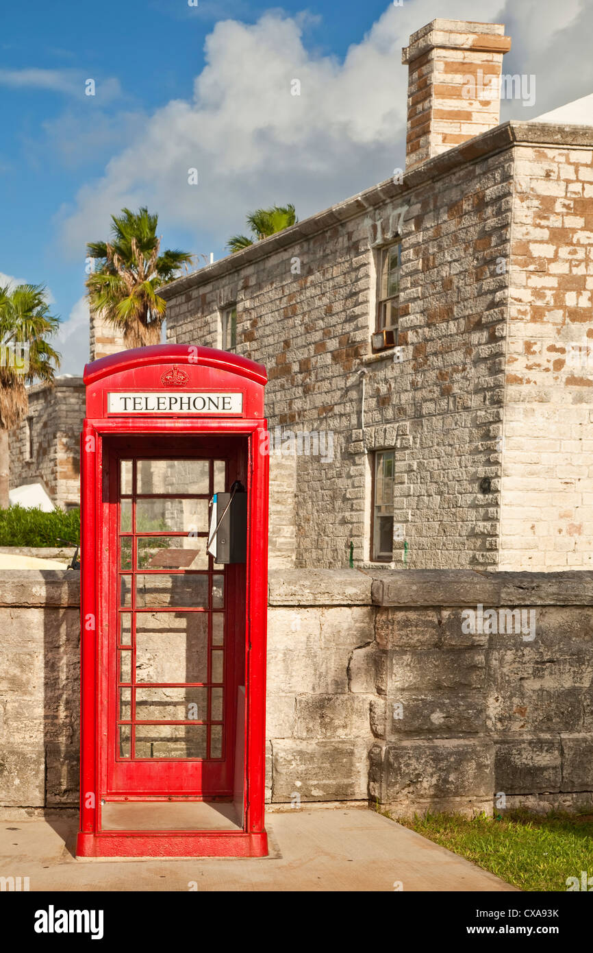 A red telephone box, typical of English influence, in the Royal Naval Dockyard, Bermuda. - Stock Image