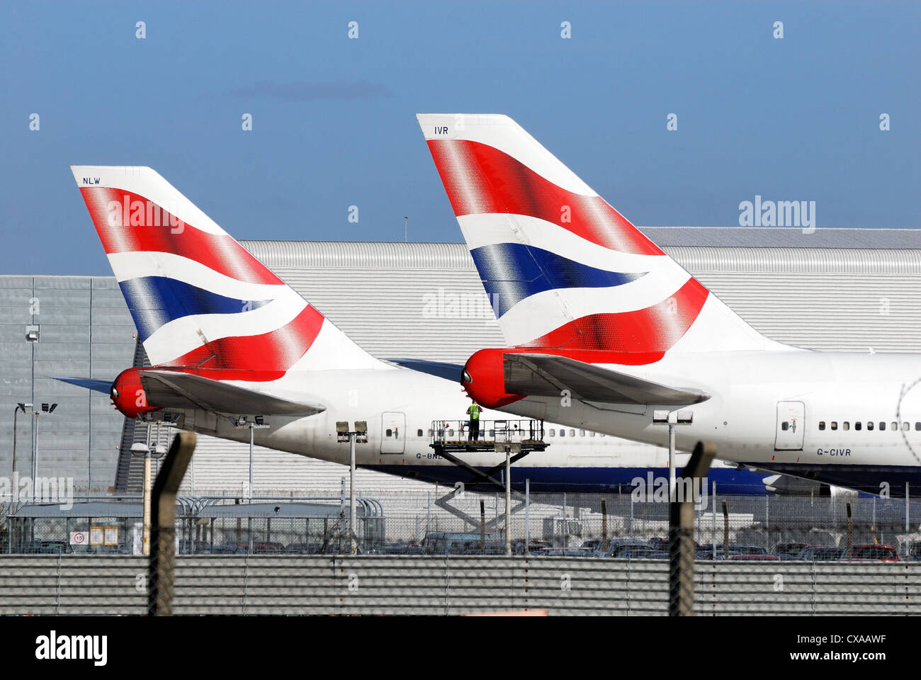 British Airways company logo on tail fins of two jet aircraft ,Heathrow London - Stock Image
