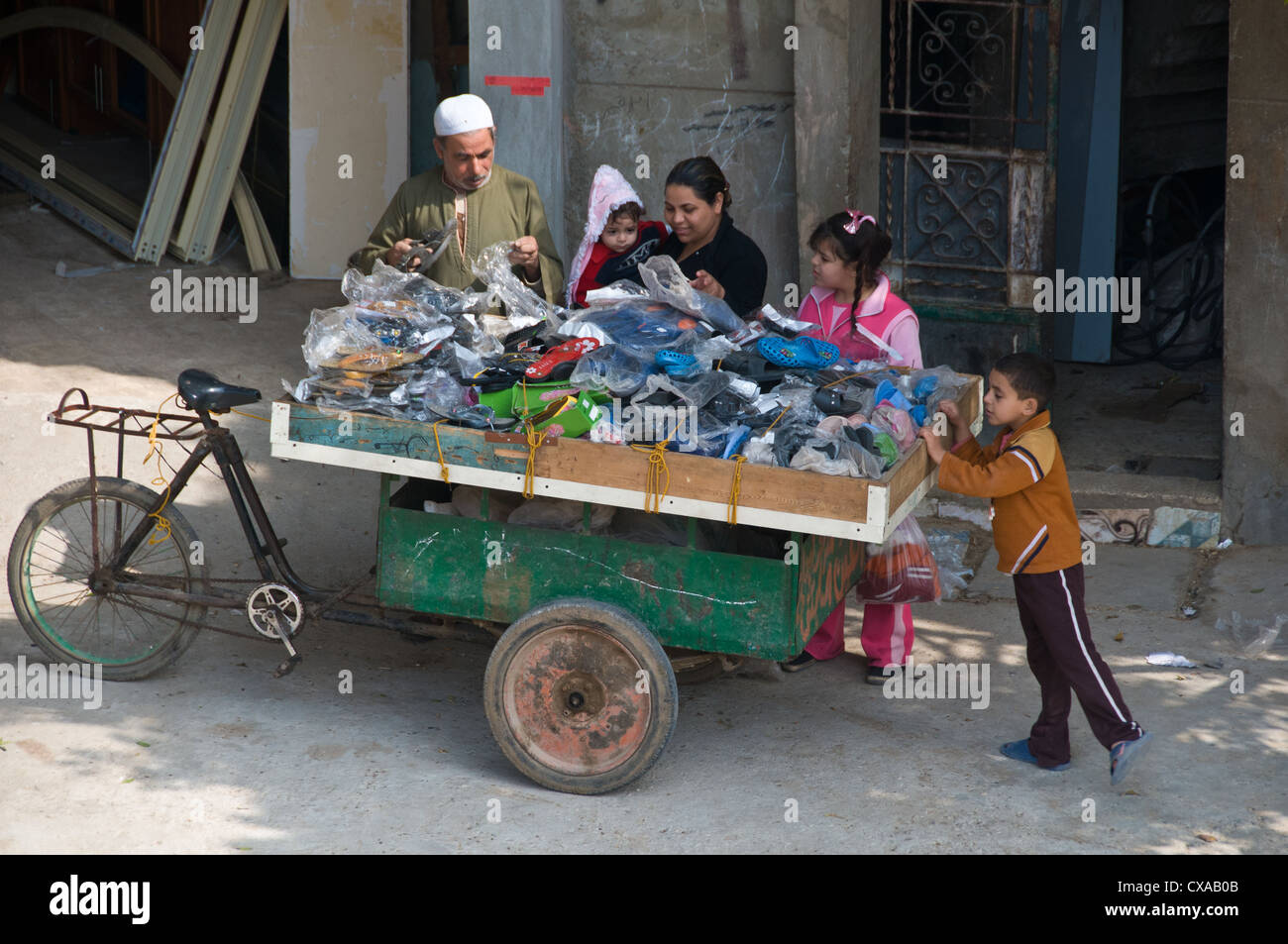 People buying from a merchant working class area Giza Cairo Egypt - Stock Image