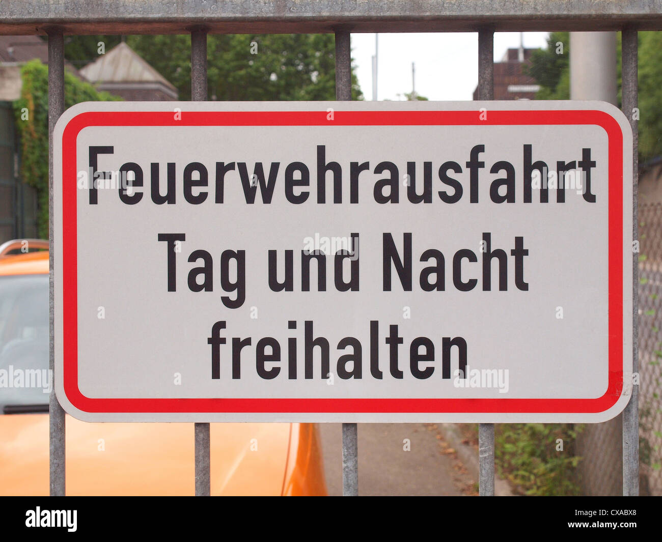 A fire lane road sign in German, meaning to leave exit free all day and night - Stock Image