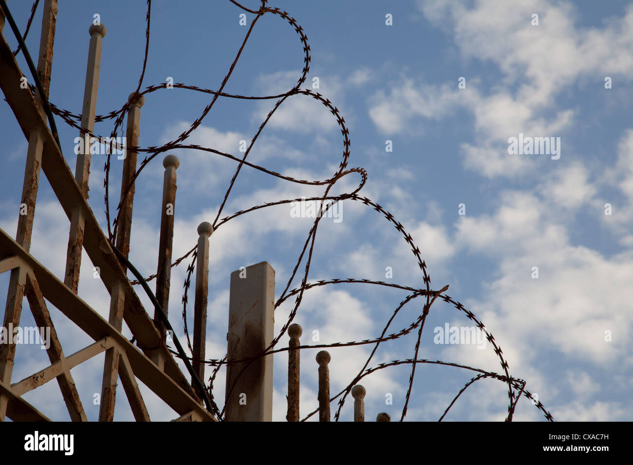Barbwire on a fence with sky and clouds background - Stock Image