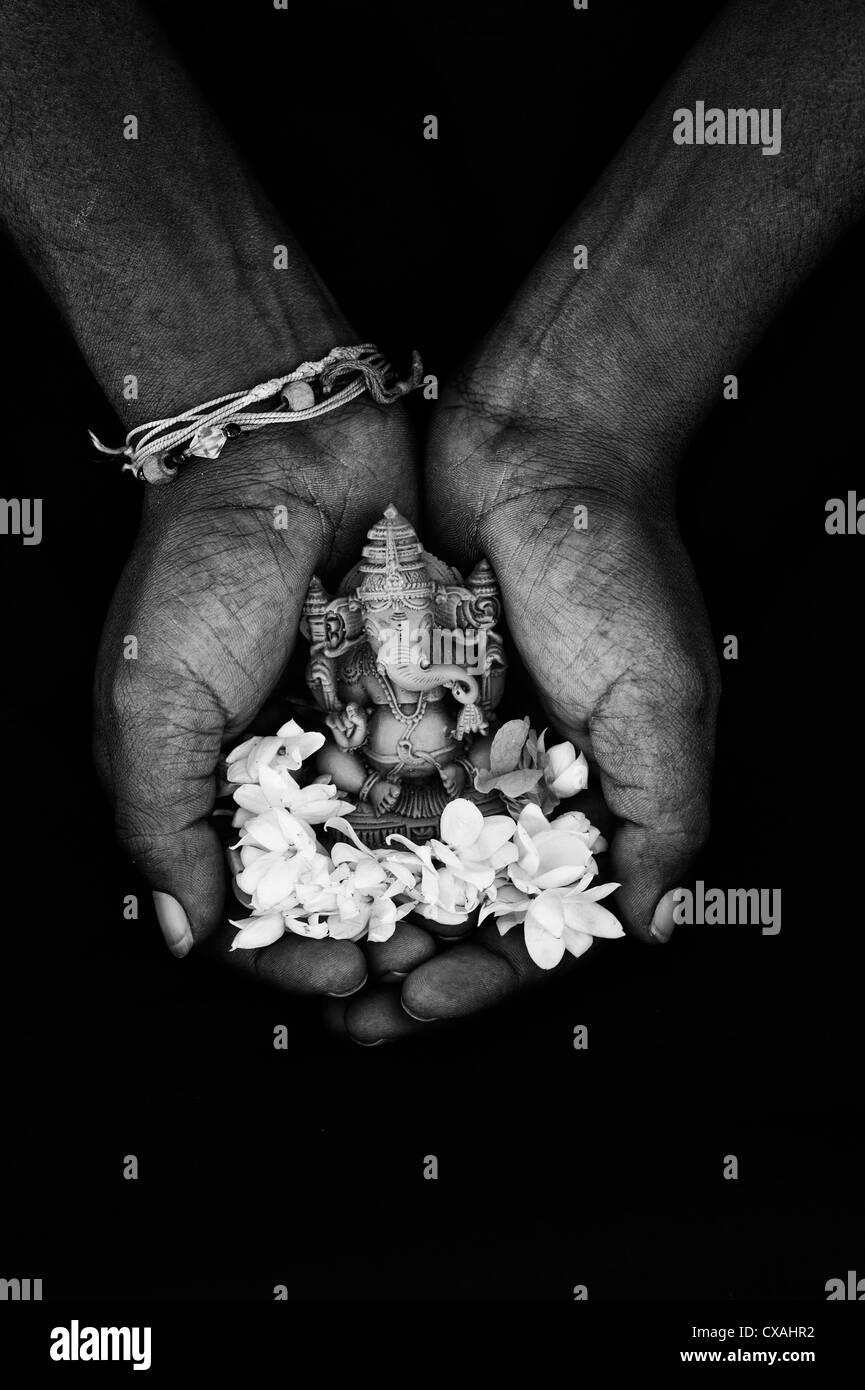 Hindu Elephant God. Indian mans hand holding Lord Ganesha statue and jasmine flowers against black background. Monochrome - Stock Image