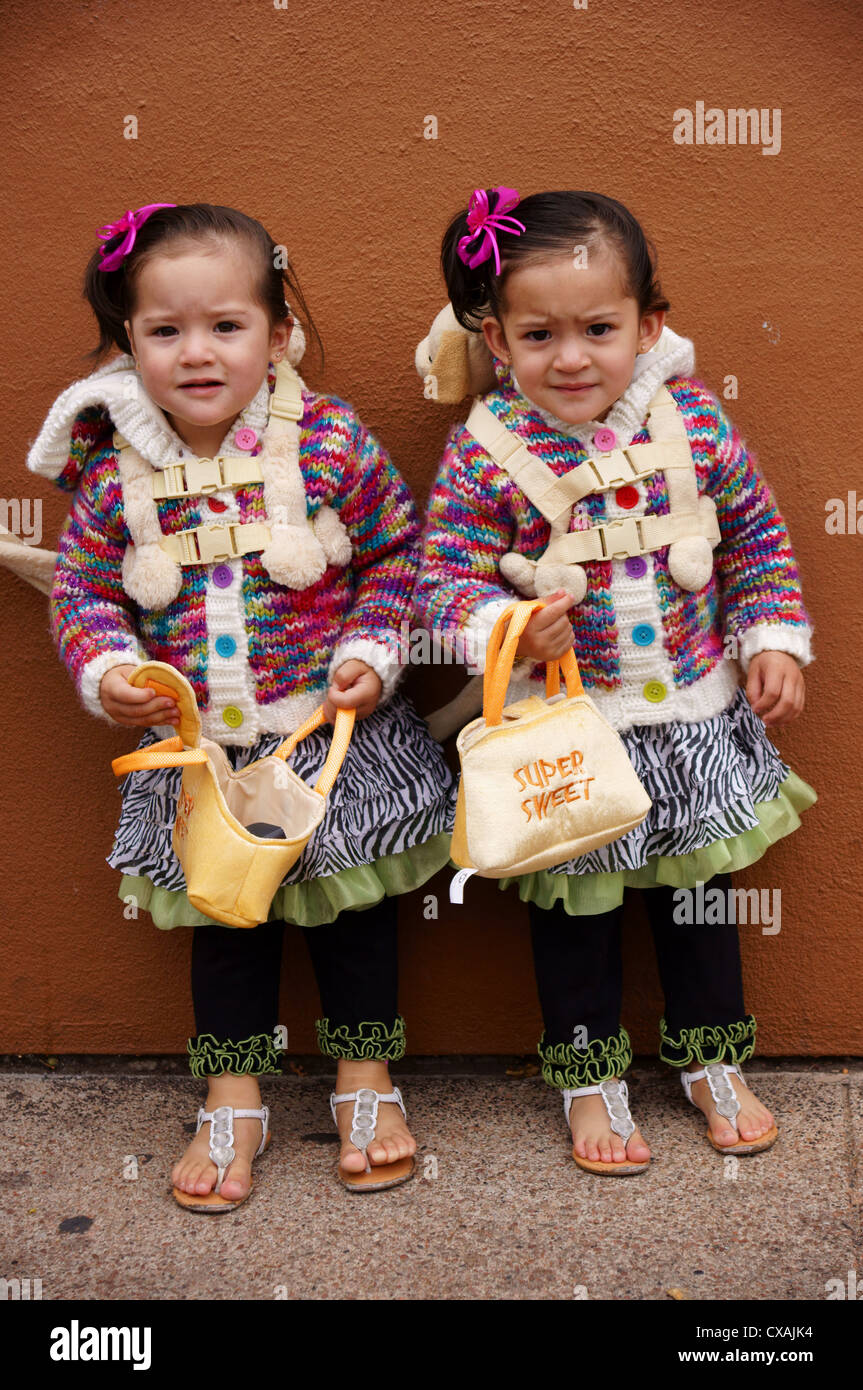portrait headshot of twin baby hispanic latino girls toddlers females in stern look wonder fear surprise cute Stock Photo