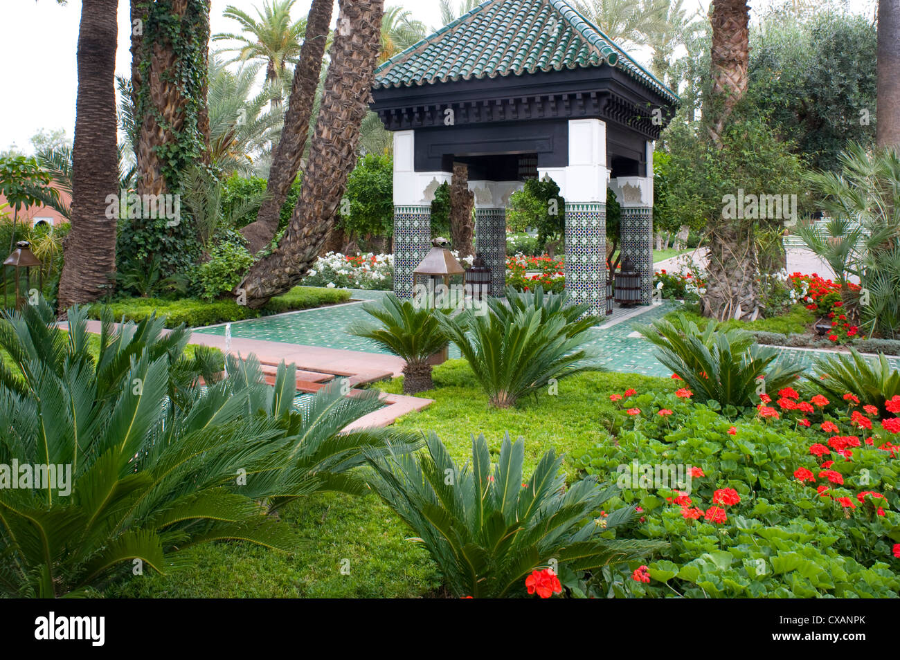 An ornately tiled pavilion surrounded by geraniums and palm trees in the garden of La Mamounia Hotel in Marrakech, - Stock Image