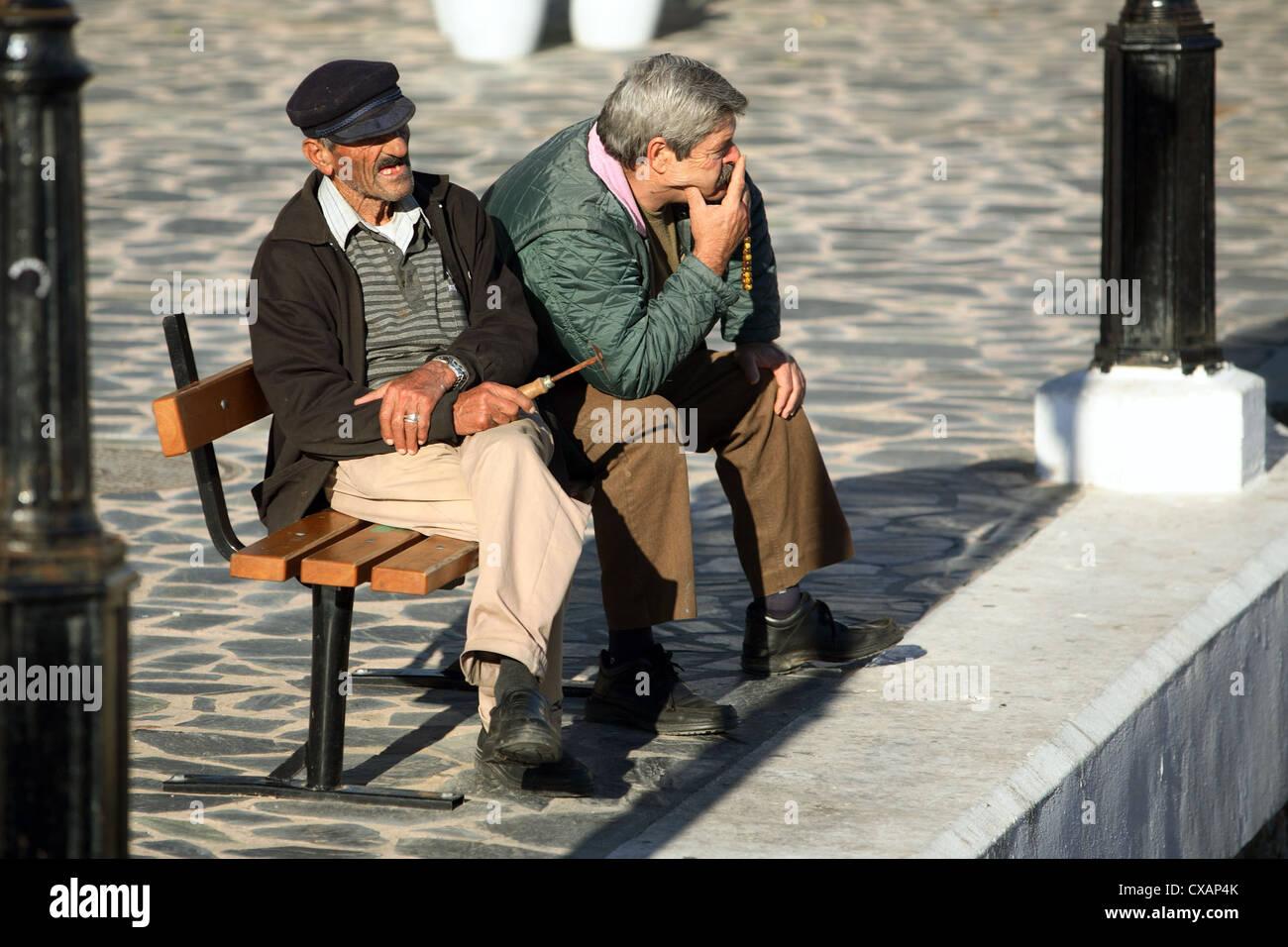 Agios Nikolaos, old men sitting on a bench - Stock Image