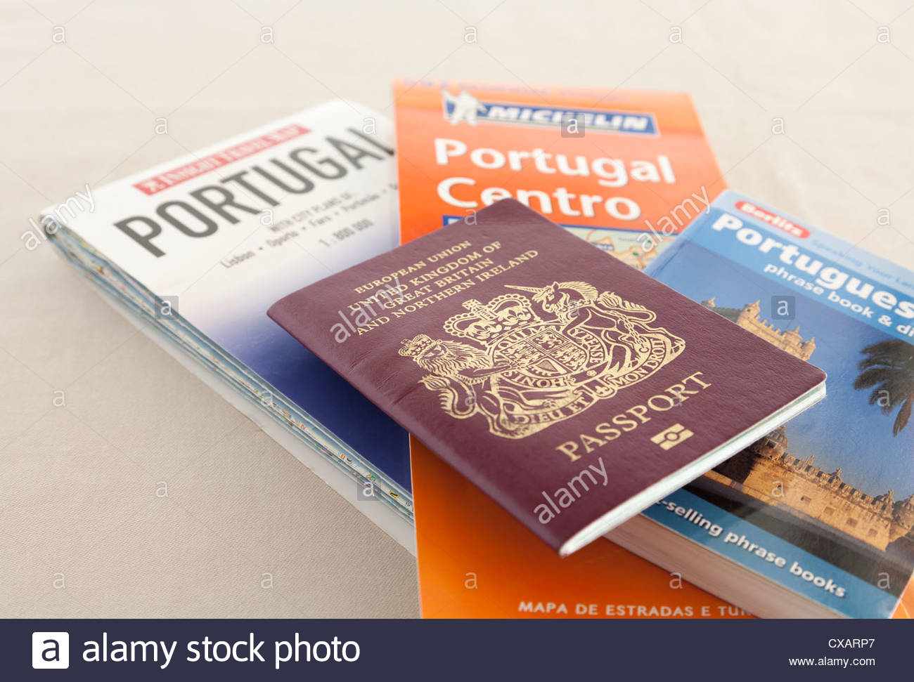 two maps of Portugal a Berlitz Portuguese phrase book and dictionary with a United Kingdom Passport Stock Photo