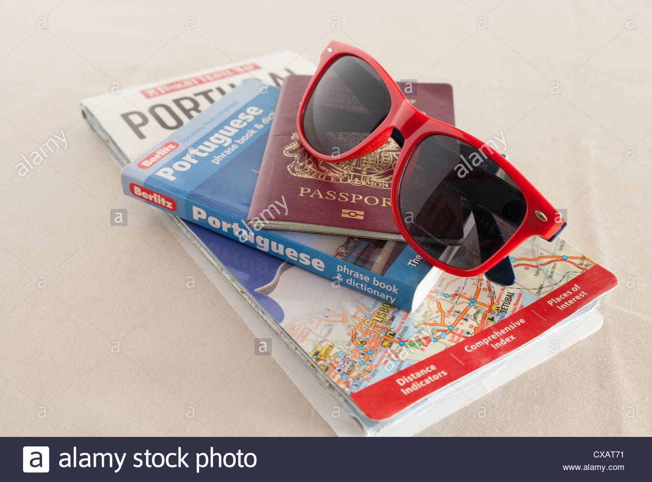 A map of Portugal with a Berlitz Portuguese phrase book and dictionary a United Kingdom Passport and a pair of Sunglasses - Stock Image