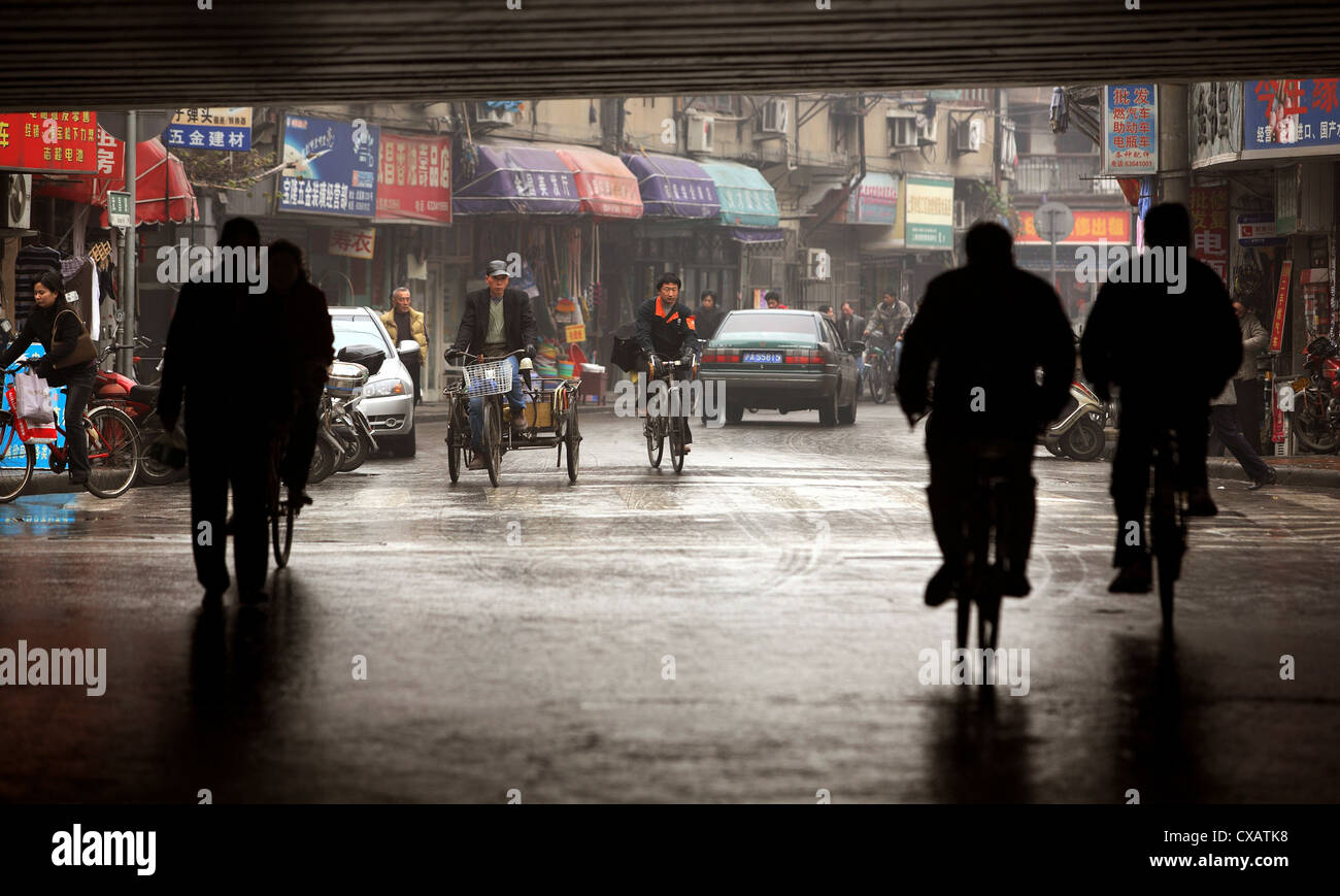 Shanghai, cyclists on a wet road Stock Photo