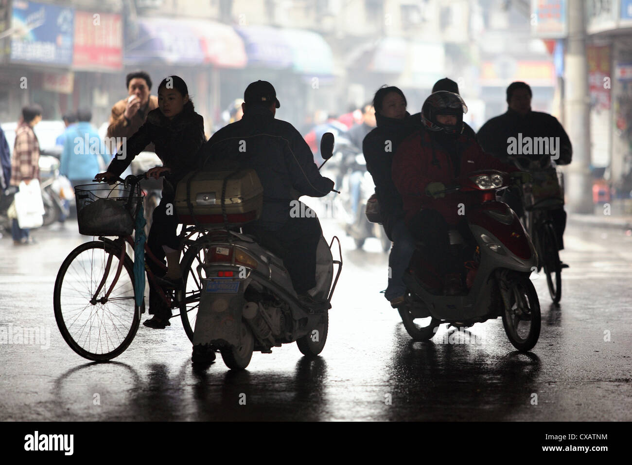Shanghai, silhouette of bicycle and motorcycle riders Stock Photo