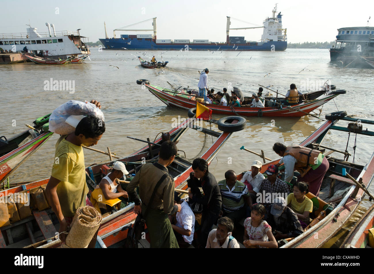Passengers embarking on a small ferry boat across the river. Yangon harbour, Myanmar (Burma), Asia - Stock Image