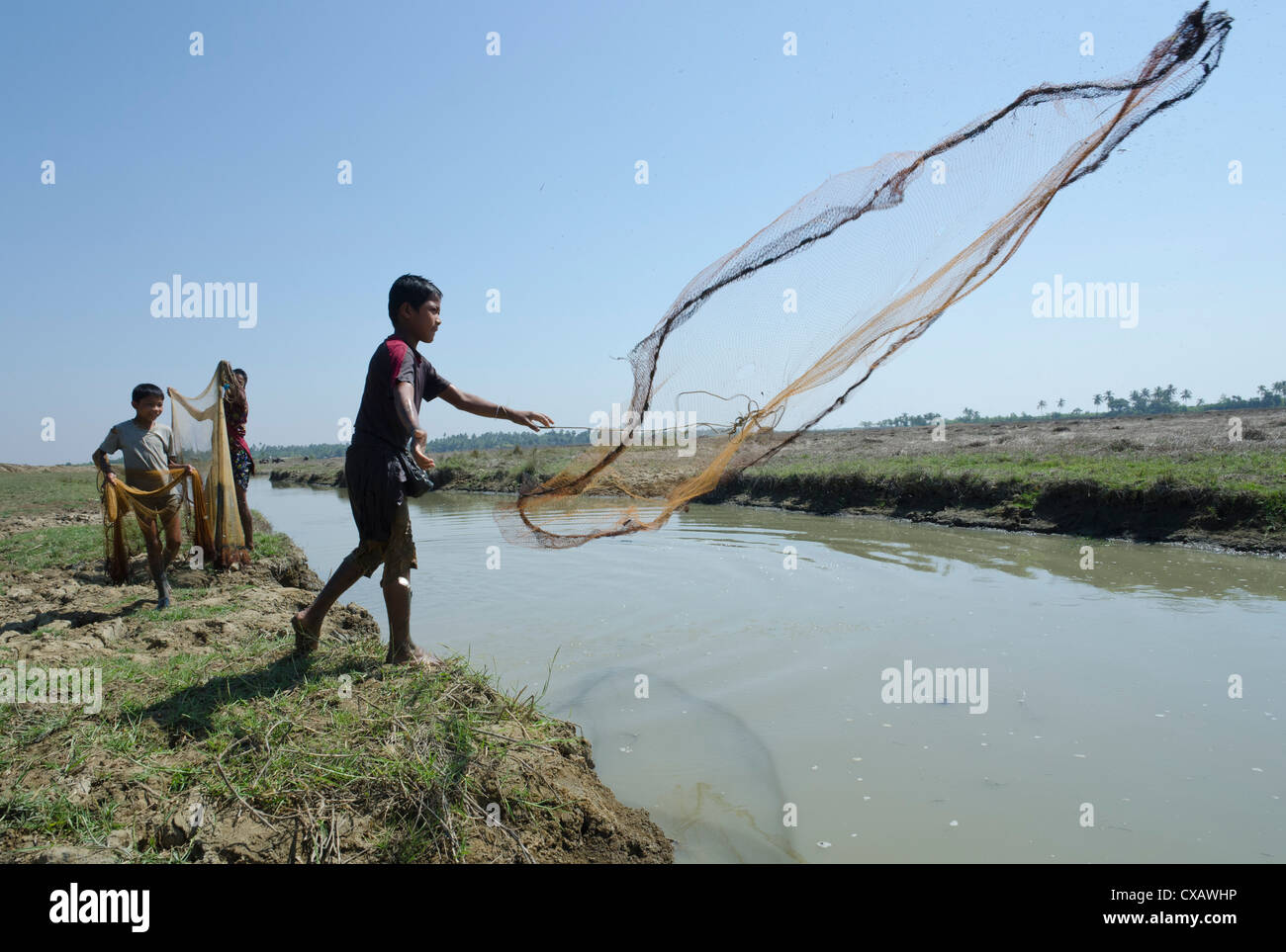 Youngsters fishing with net in waterway, Irrawaddy Delta, Myanmar (Burma), Asia - Stock Image