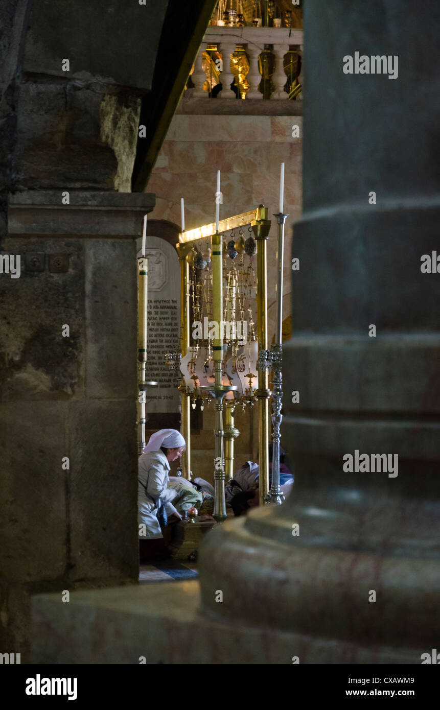 Female pilgrims prostrating at the Stone of Anointing seen through colums. Holy Sepulchre, Old City, Jerusalem, - Stock Image