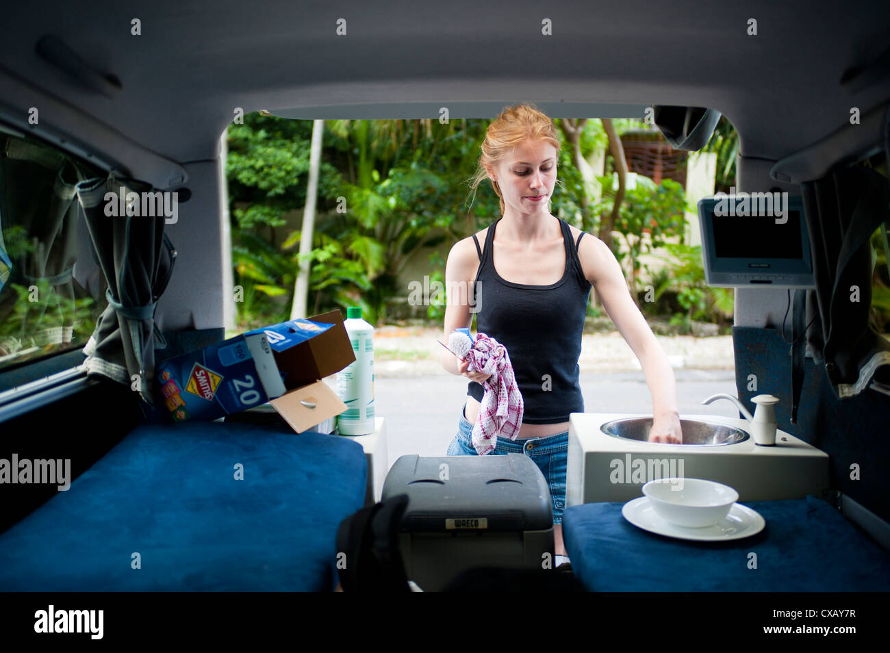 Woman washing up in a campervan, Byron Bay, New South Wales, Australia, Pacific - Stock Image