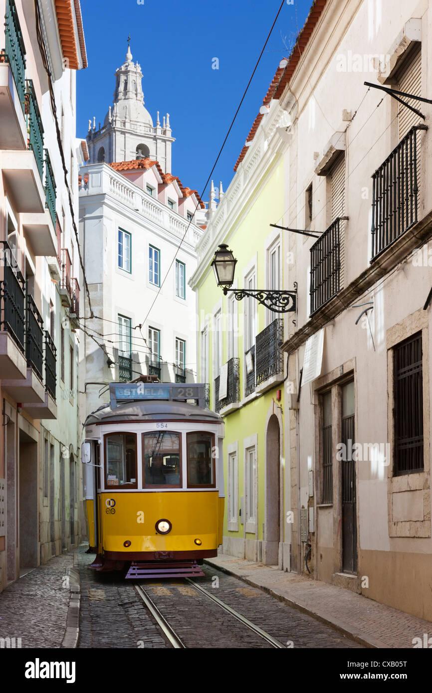 Tram (electricos) along Rua das Escolas Gerais with tower of Sao Vicente de Fora, Lisbon, Portugal, Europe - Stock Image