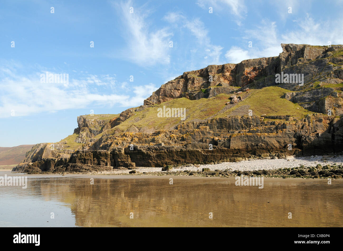 Coastal cliffs at Rhossili, viewed from below at low tide, The Gower peninsula, Wales, United Kingdom, Europe - Stock Image
