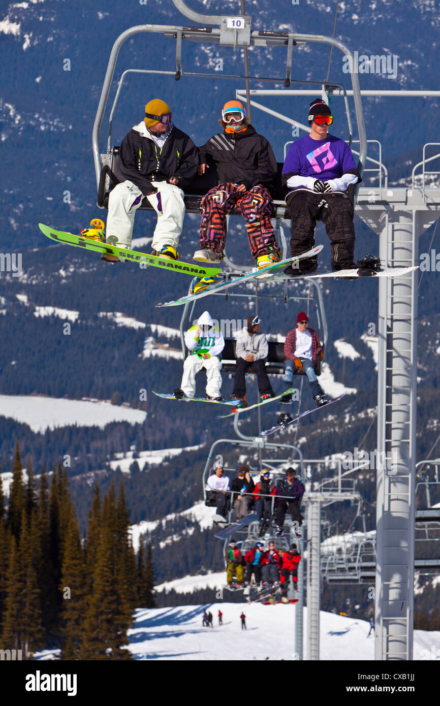 Chairlift carrying skiers and snowboarders, Whistler Mountain, Whistler Blackcomb Ski Resort, Whistler, British - Stock Image
