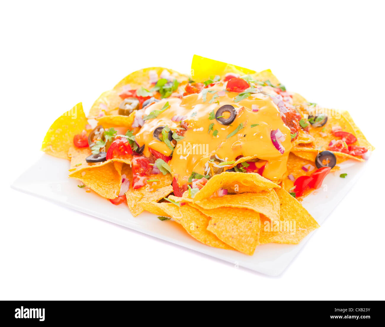 Plate of fresh nachos with a spicy jalapeno cheese sauce - Stock Image