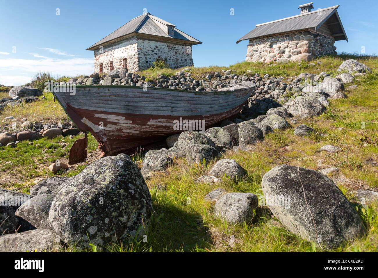 Old boat and stone houses on the shore. Bolshoi Zayatsky Island, Solovetsky Islands, The White Sea, Karelia, Russia. Stock Photo