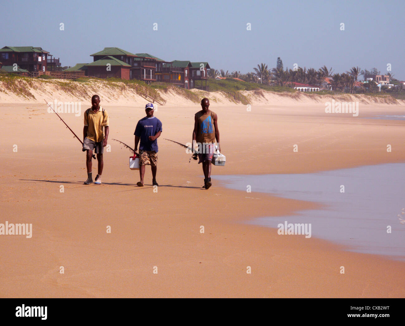 Men going fishing at Coco Cabanas beach resort. Ponta do Ouro, southern Mozambique. - Stock Image