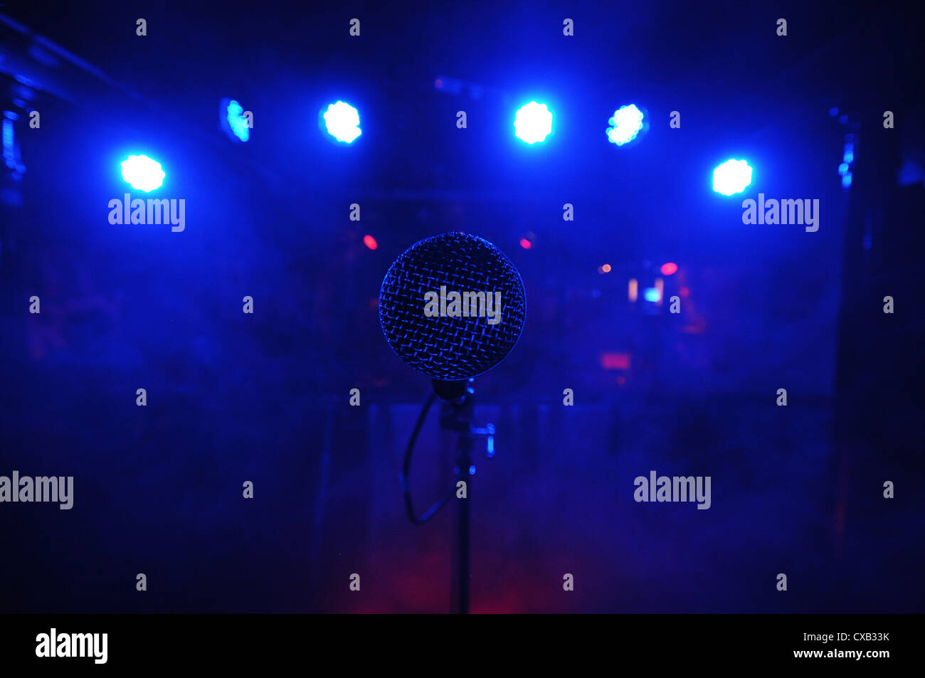 Microphone on the stage with blue lights. - Stock Image