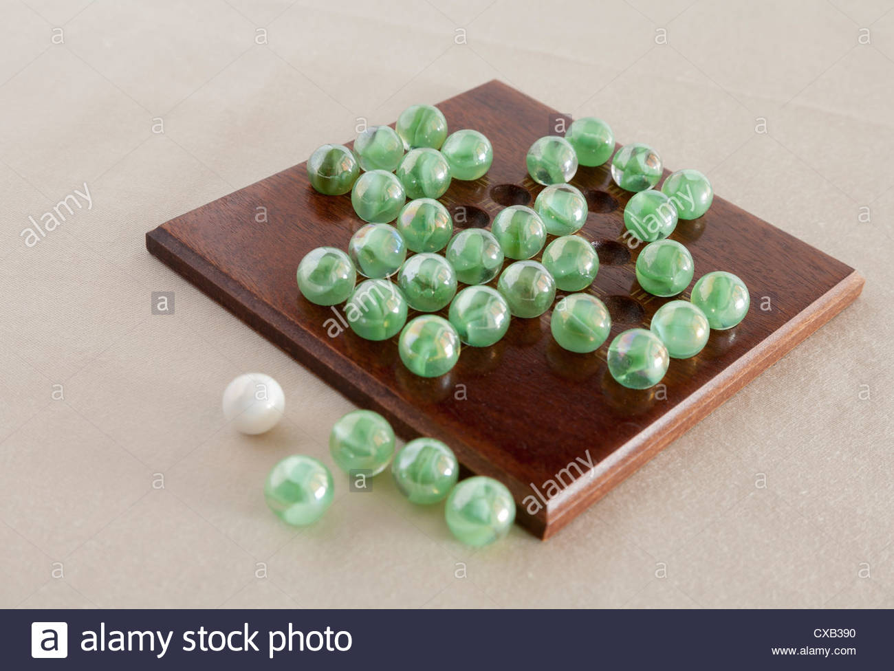 glass marble solitaire game on wooden board - Stock Image