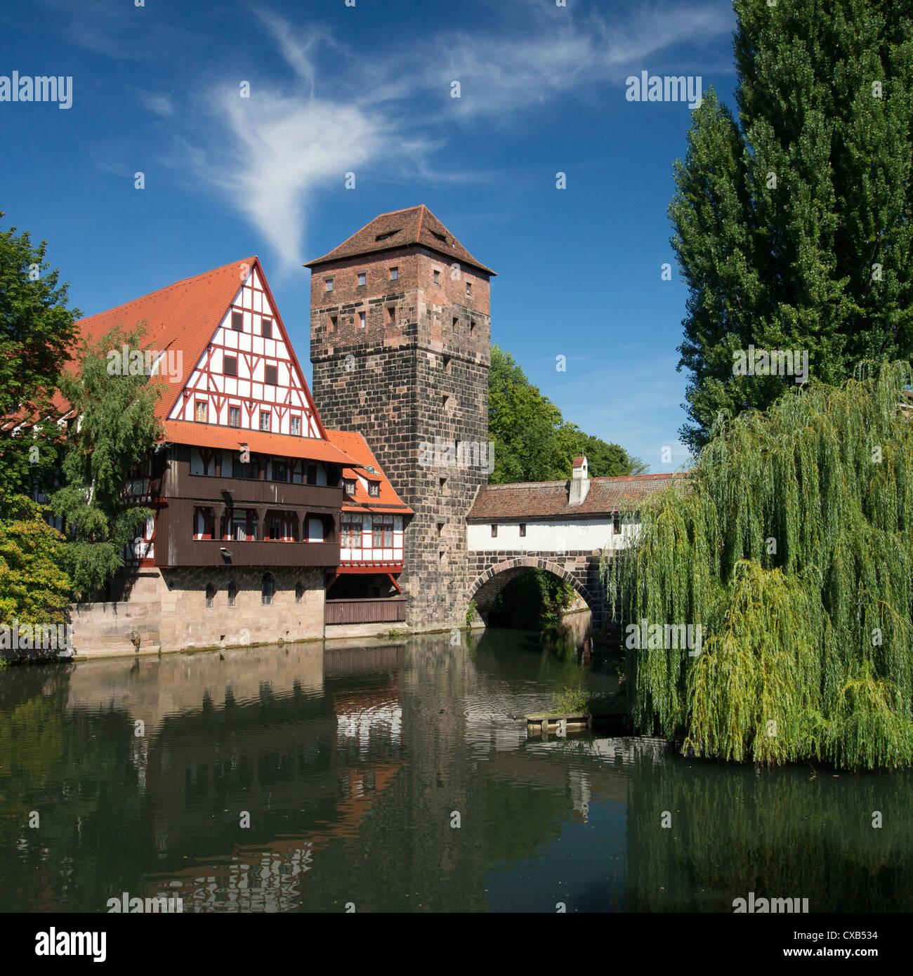 View of historic Wine Vault or Weinstadel, water tower and Hangman's Way or Henkersteg beside Pegnitz River - Stock Image