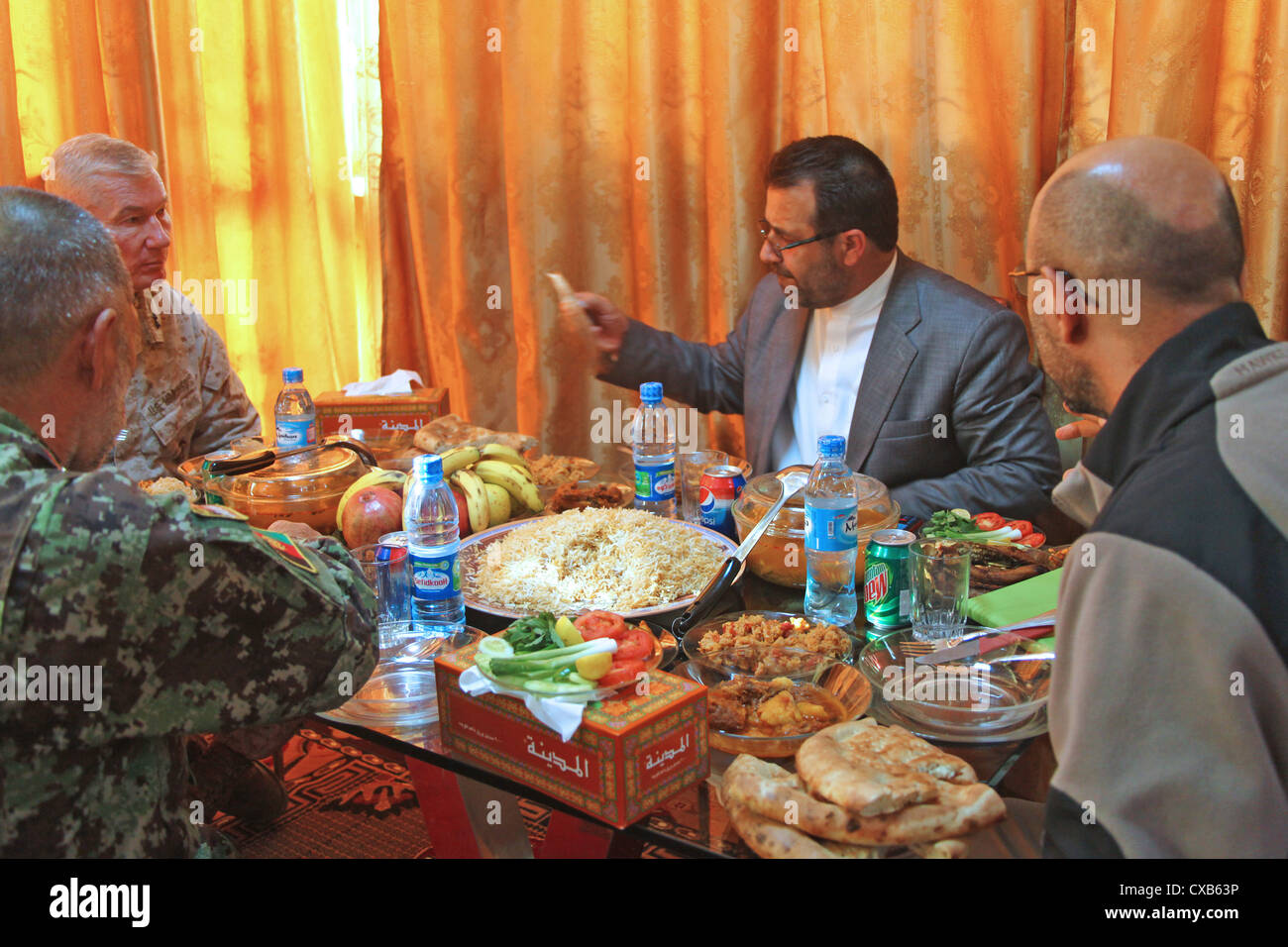 Major General John Toolan (far left) talks over lunch with Helmand Provincial Governor Gulab Mangal November 28, Stock Photo