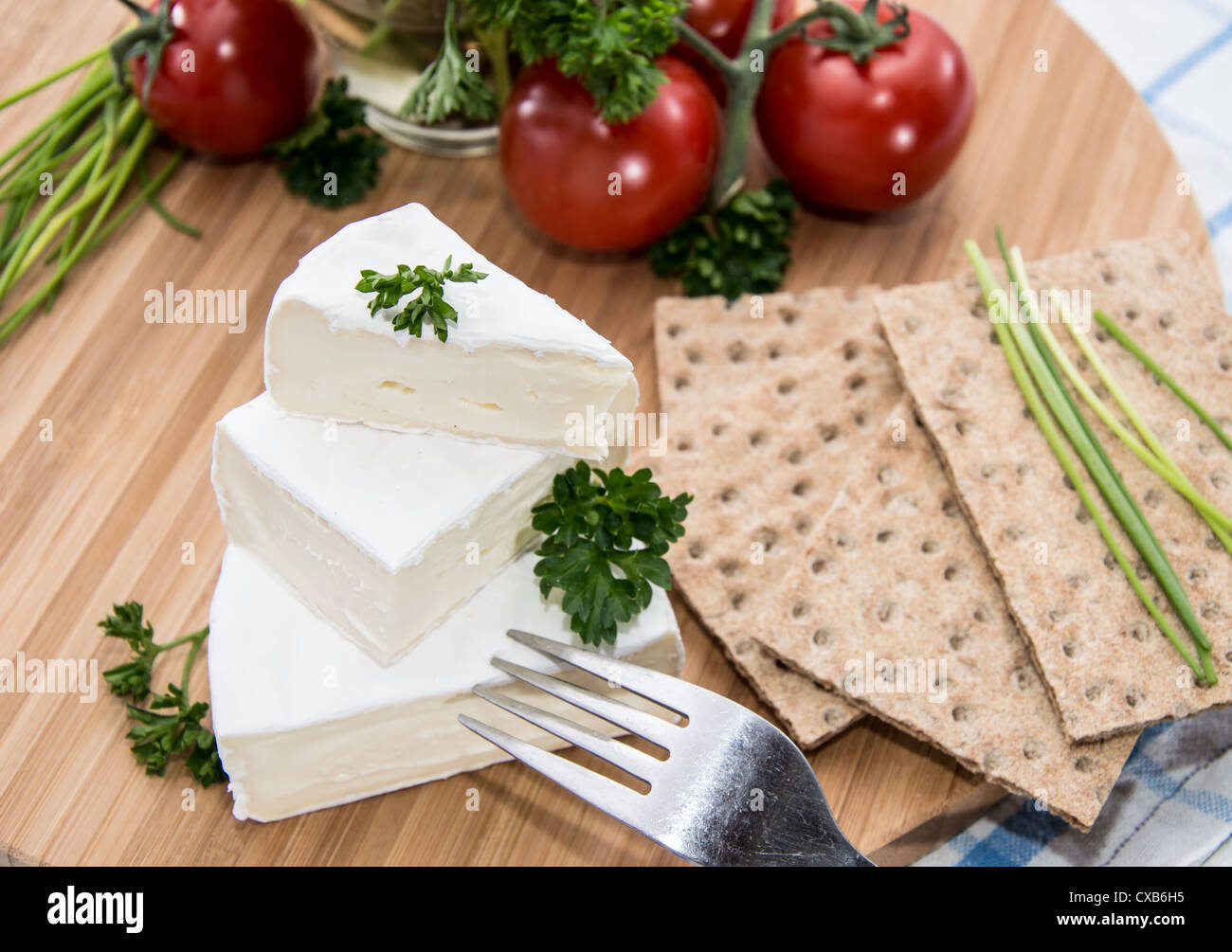 Camembert with Crispbread and Herbs on a cutting board - Stock Image
