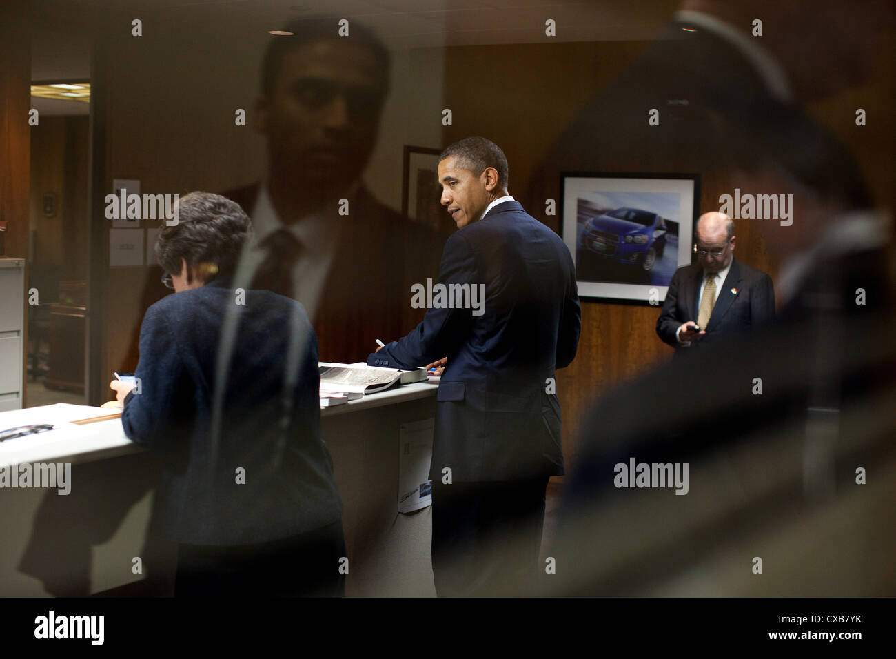 US President Barack Obama is seen through a window backstage at the General Motors Lake Orion Assembly Plant October - Stock Image