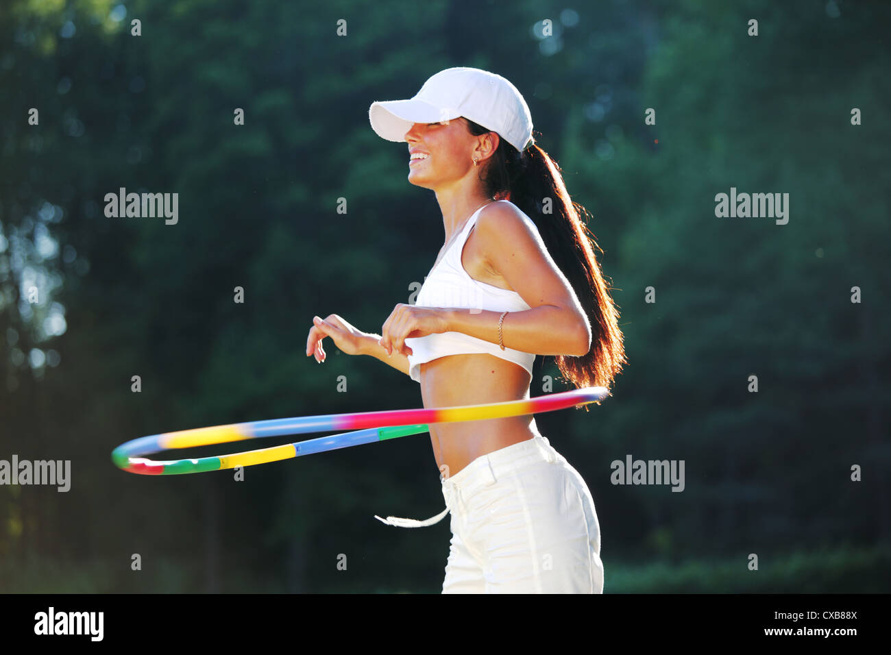 woman rotates hula hoop on nature background Stock Photo