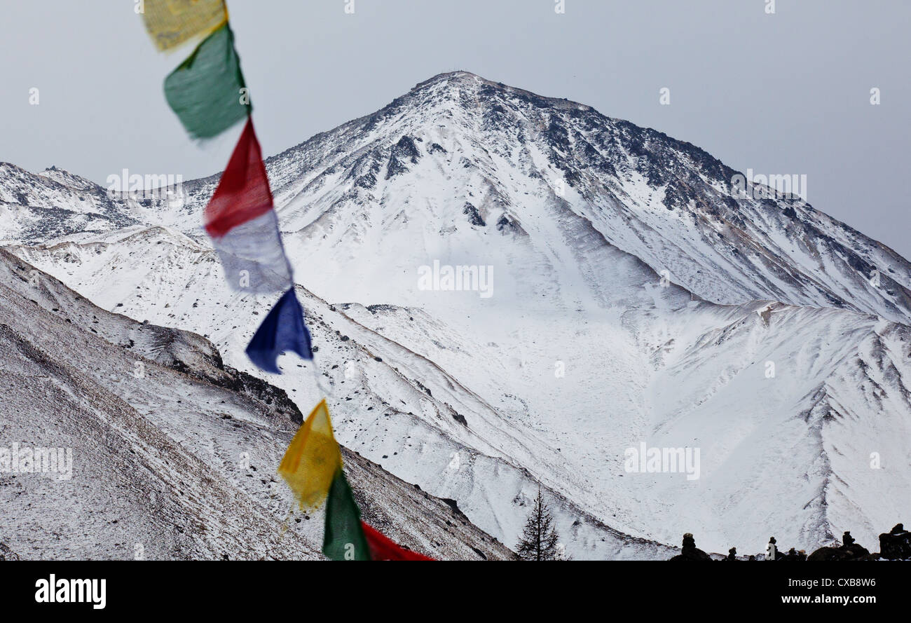 Colourful buddhist prayer flags blowing in the wind with a mountain in the distance, Langtang Valley, Nepal - Stock Image