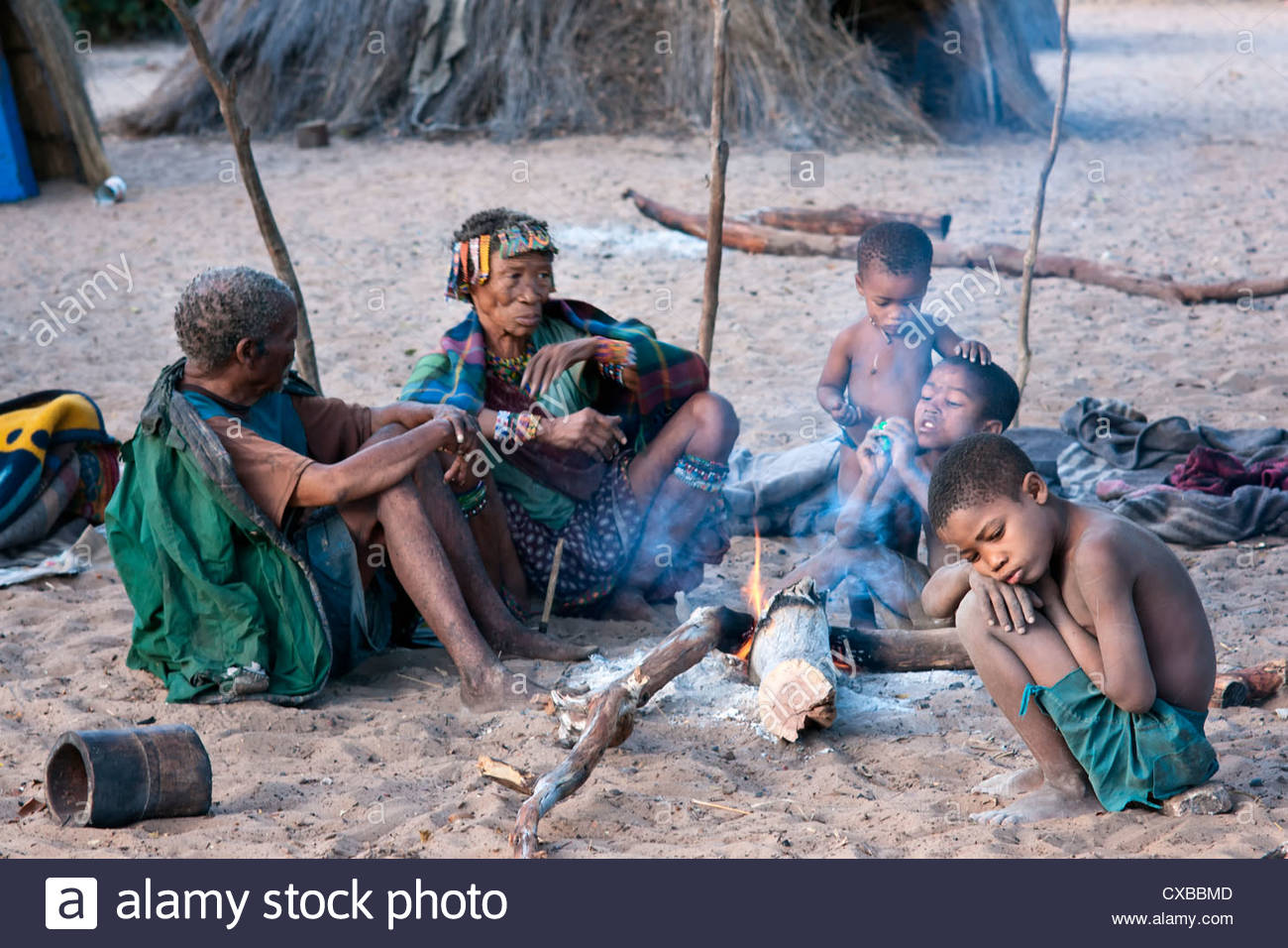 Jul'hoan !Kung Bushmen family around a fire in their village, Bushmanland, Kalahari Desert, Namibia, Africa - Stock Image