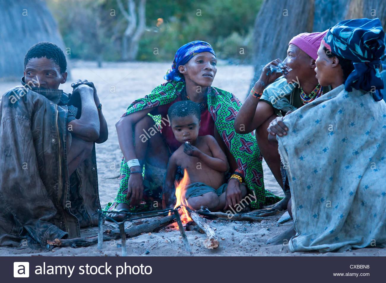 Jul'hoan !Kung Bushmen family around a fire in their village, Bushmanland, Kalahari Desert, Namibia, Africa - Stock Image