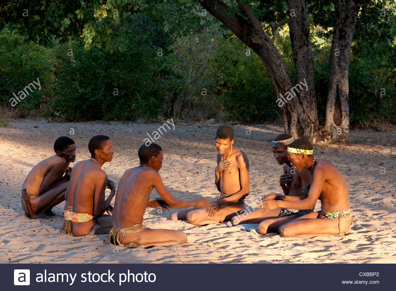 Jul'hoan !Kung Bushman sitting in sand playing a traditional game, Bushmanland, Kalahari Desert, Namibia, Africa - Stock Image