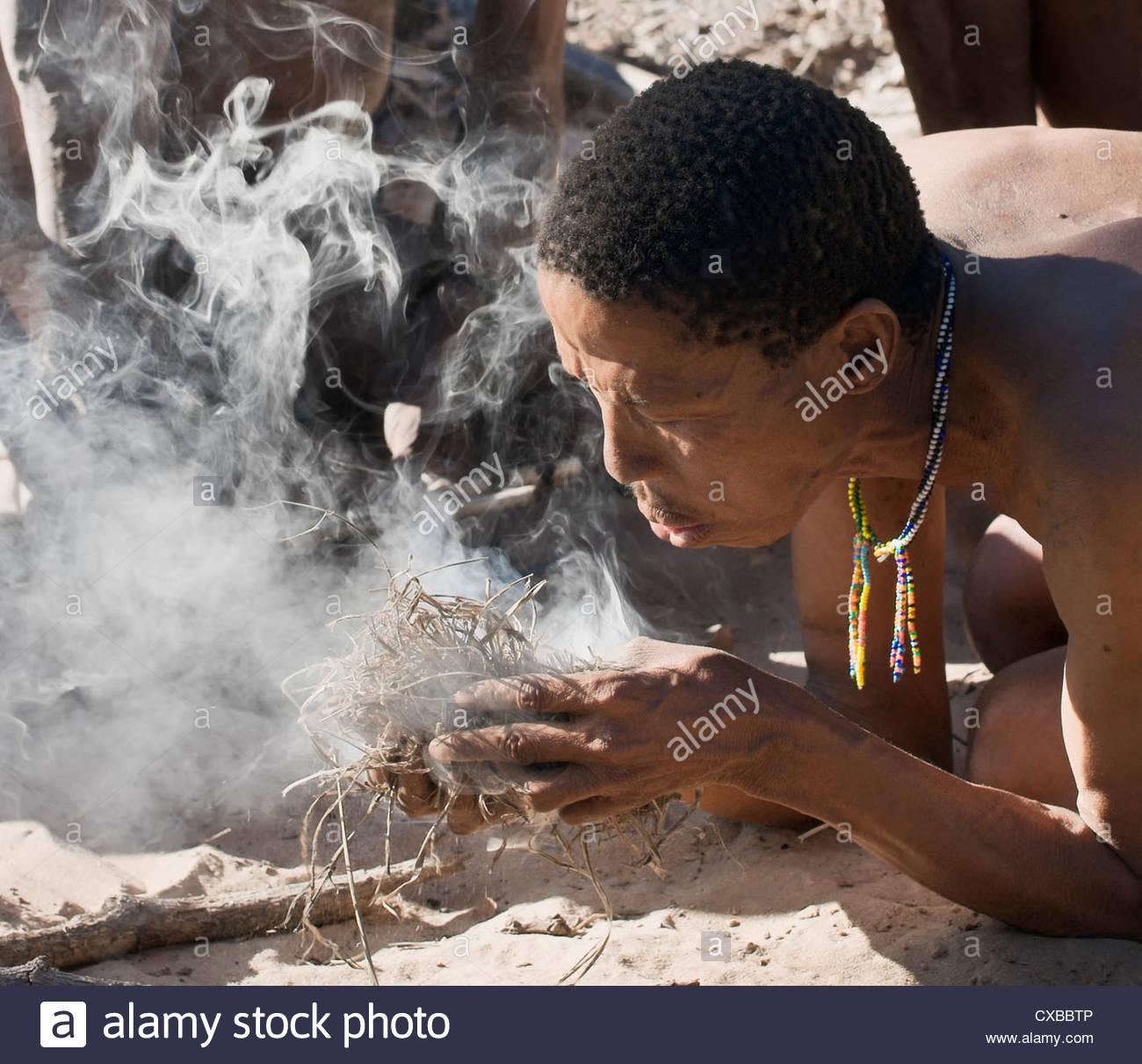 Jul'hoan !Kung Bushmen starting a fire using friction, Bushmanland, Kalahari Desert, Namibia, Africa - Stock Image