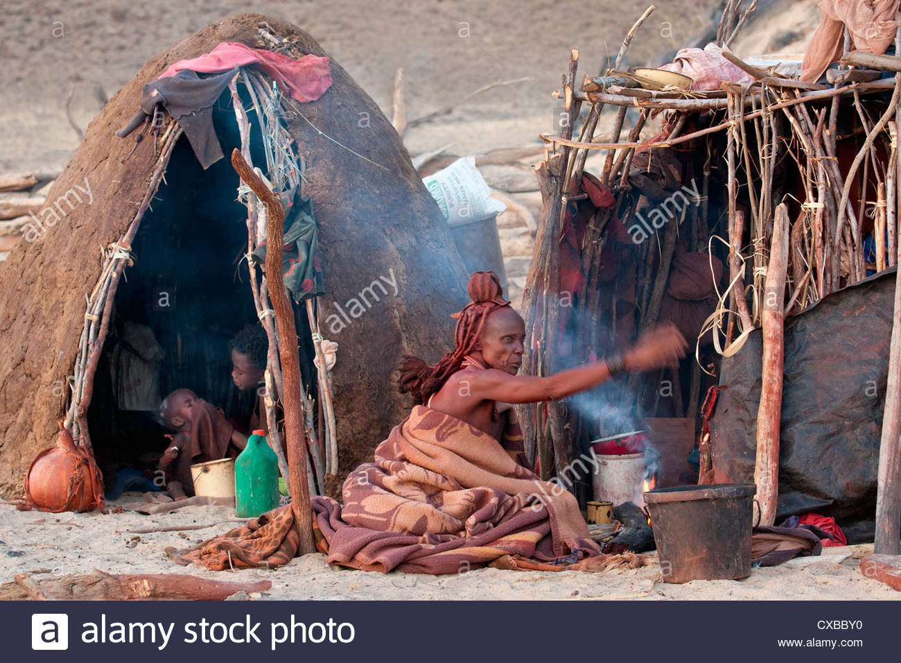 Himba woman sitting on ground fanning a small fire outside two huts, Himba village, Purros, Namibia, Africa - Stock Image
