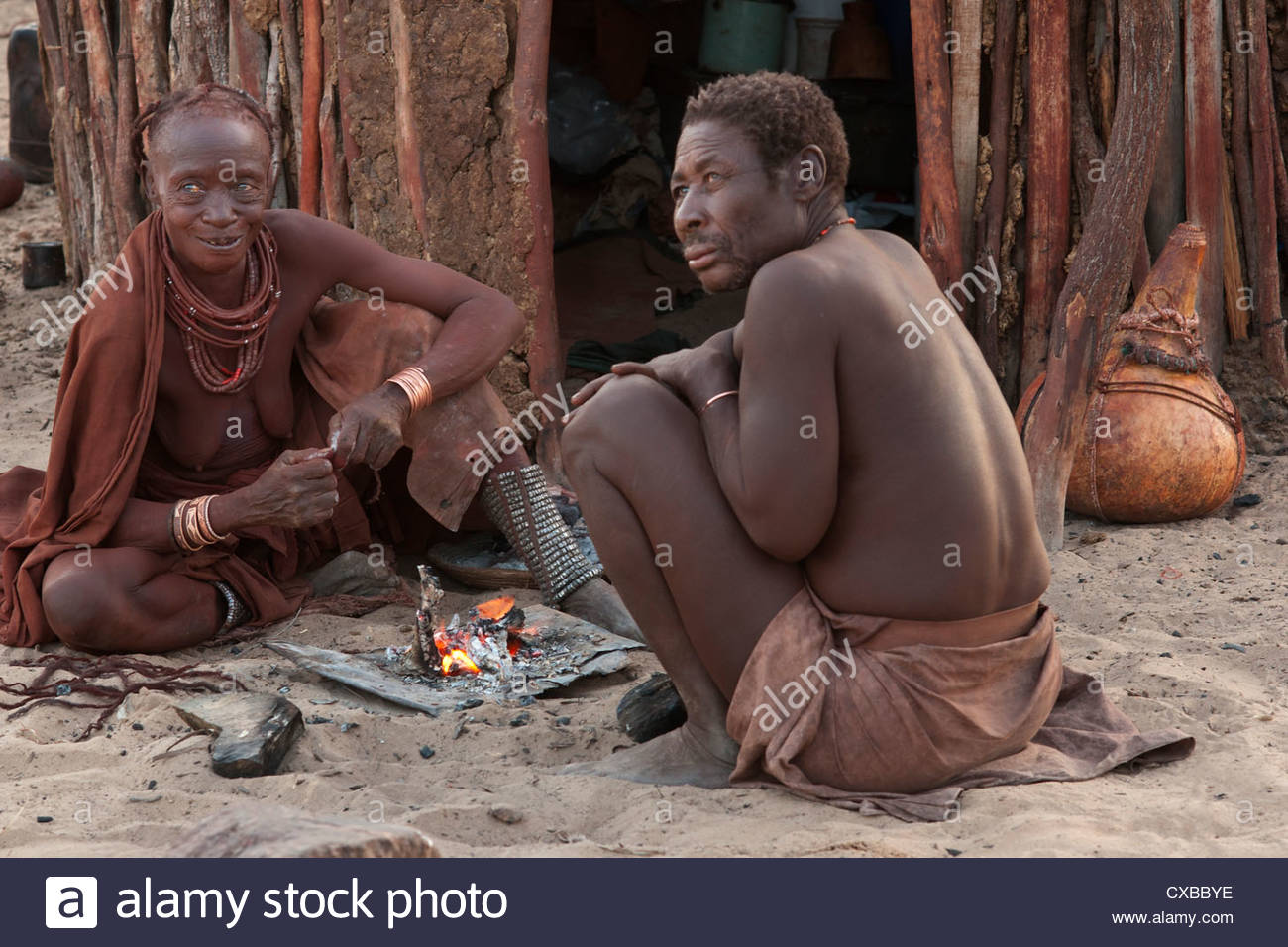 Elderly Himba married couple sitting near a small fire outside their hut, Purros village, Namibia, Africa - Stock Image