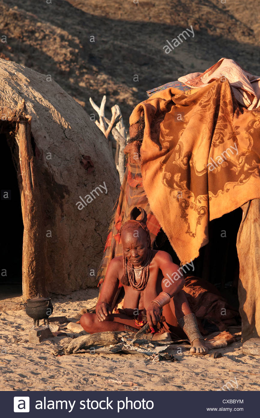 Himba woman sitting outside her hut, Purros village, northern Kaokoland, Namibia, Africa - Stock Image