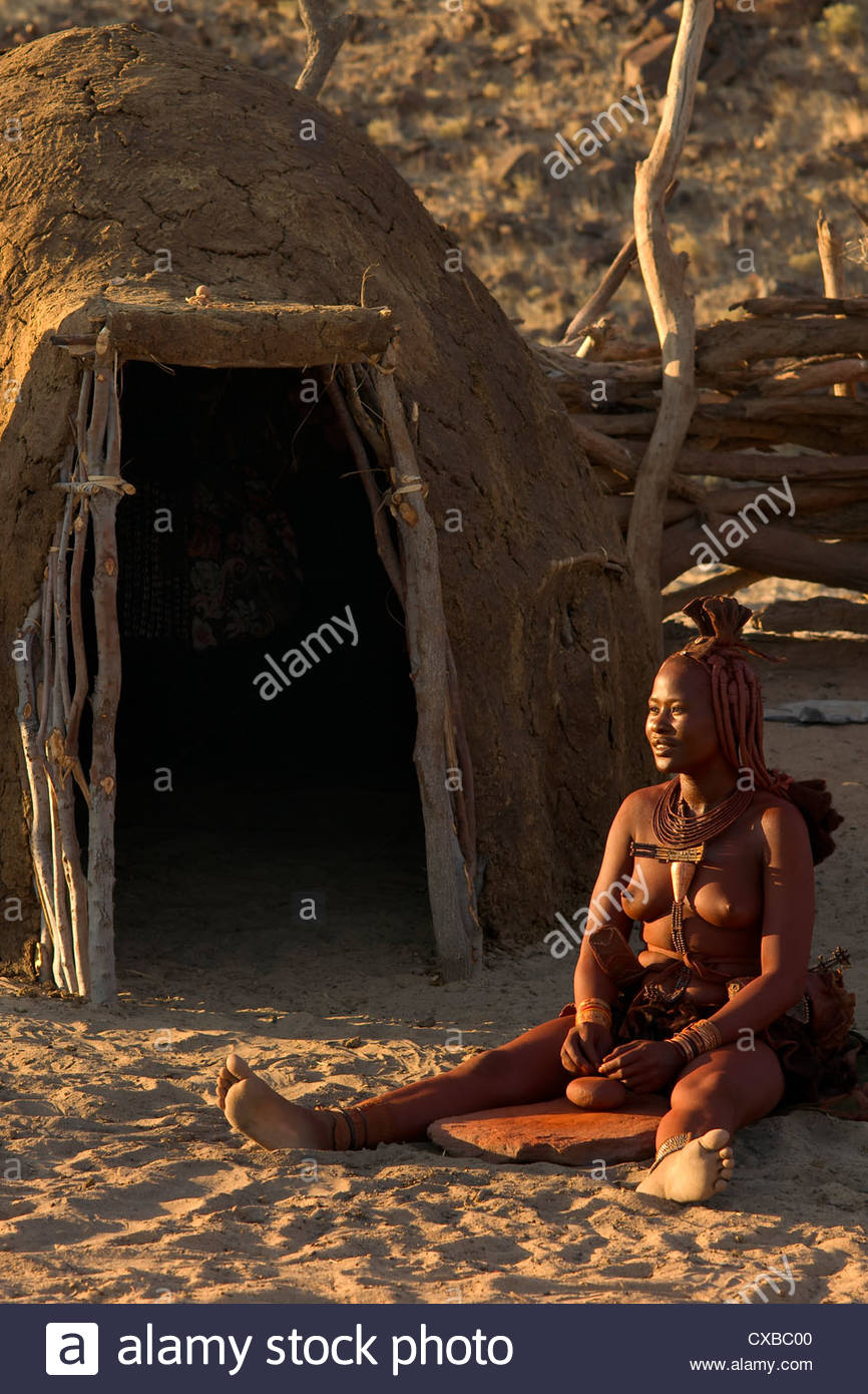Himba woman sits outside her mud hut grinding rock into powder for body application, Purros village, Kaokoland, - Stock Image
