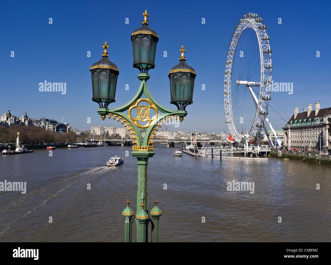 Ornate historic lanterns on Westminster Bridge with London Eye and sightseeing pleasure boat River Thames Westminster - Stock Image